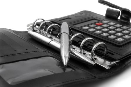 A black diary with calculator and two silver pens. photo