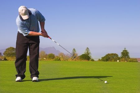 Golfer putting on the green. Golf ball in motion. Copy space.