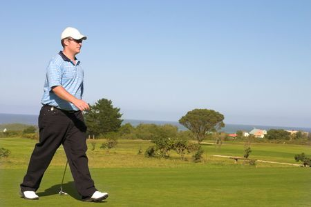Golfer walking on the golf course. Copy space. photo