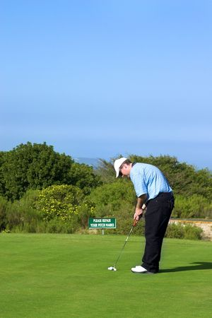 Golfer putting on the green. photo
