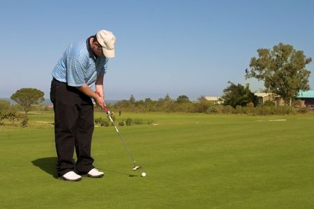 Golfer putting on the green. Golf and ball in motion. Copy space. photo