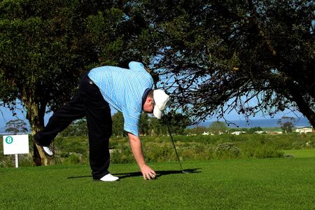 Golfer putting the ball on the grass at the tee box.