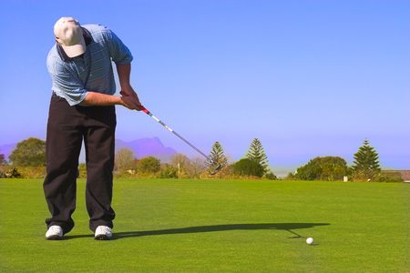 Golfer putting on the green. Stock Photo