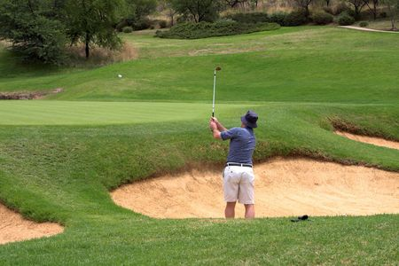 Golfer hitting the ball out of the sand bunker straight onto the green. The golf ball is flying in the air. photo