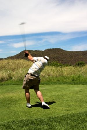 Sexy golfer with trained culfs hitting the ball from the tee box. Golf club is in motion. photo