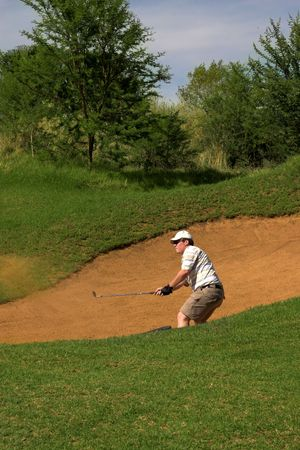 Golfer hitting the ball out of the sand bunker. Sand and golf club are in motion photo