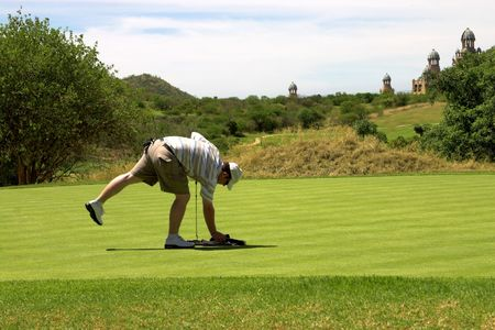 Golfer picking up the towel on the green. photo