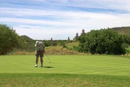 Golfer putting on the green. Golf ball is moving. photo