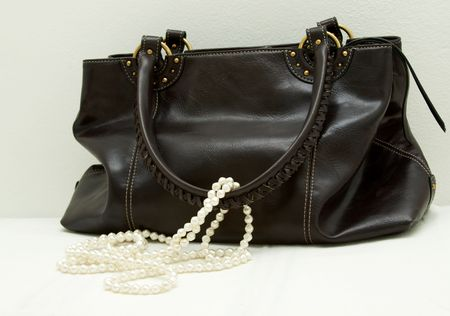 Brown leather bag with white pearls on white background. photo