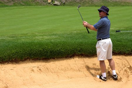 Golfer in the sand bunker. Happy because he landed the ball right next to the hole. photo