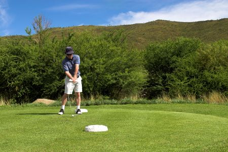 Golfer hitting the ball from the tee box. Hands and club are in motion. photo