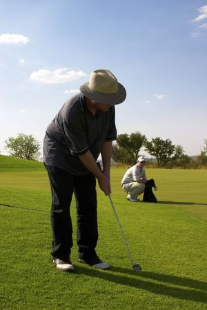Two golfers on the green. One putting, and another one looking at the camera. photo