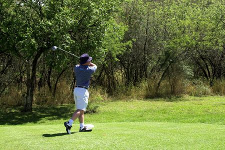 Golfer in striped shirt playing from the tee box. photo