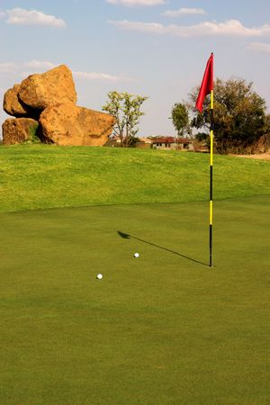 Red flag with two balls lying next to it on the green. photo