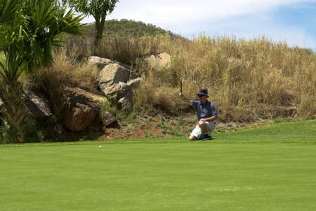 estimating: Golfer estimating the line for the put on the green. Golf ball is on the green.