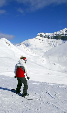 Girl snowboarding on the backdrop of scenic view in Canadian\ Rocky mountains ski resort