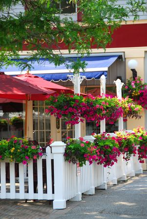 tent city: Pretty restaurant patio decorated with purple petunia flower boxes and baskets