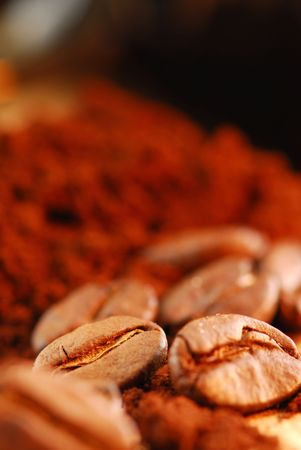 Macro image of coffee beans and ground coffee with black coffee cup photo