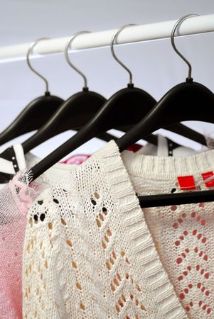 Womens clothing on a rack on black hangers
