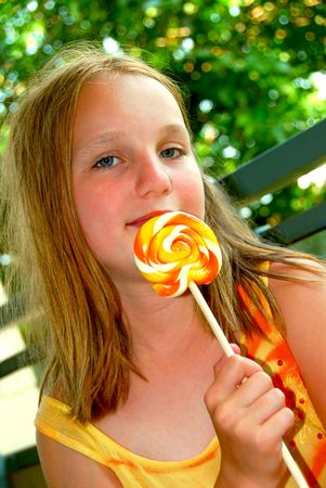 Young girl holding a big colorful lollipop candy photo
