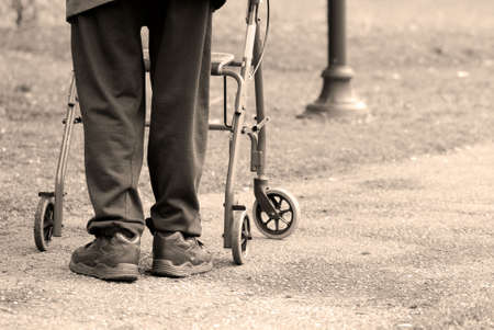 Senior man taking a walk in a park with the aid of a walking frame