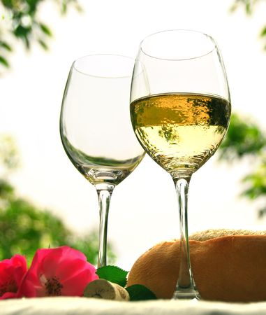Two wineglasses with white wine on the table outside photo