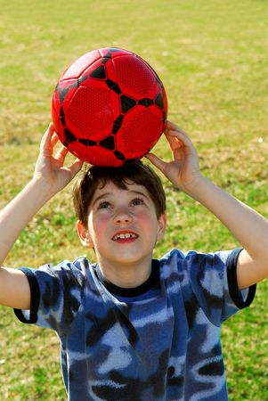 Young cute happy boy balancing a red soccer boy on his head outside photo