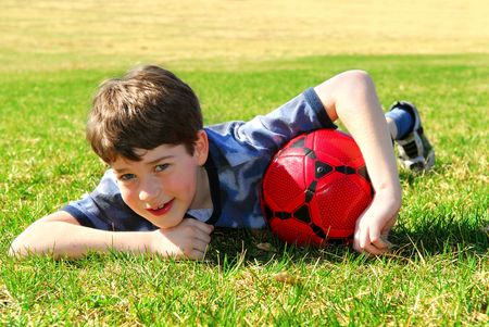 children at play: Young cute happy boy lying on grass with red soccer ball