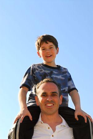 shoulder ride: Retrato de un padre y su hijo jugando al aire libre  Foto de archivo