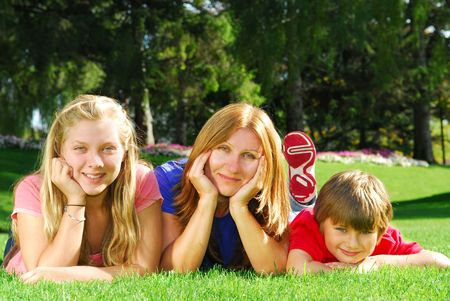 Portrait of a family - mother and children - relaxing in summer park photo