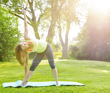 Female fitness instructor doing yoga extended triangle pose outdoors in morning sunshine photo