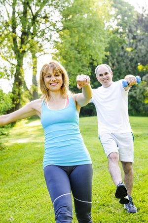Female fitness instructor exercising with middle aged man outdoors in green park photo