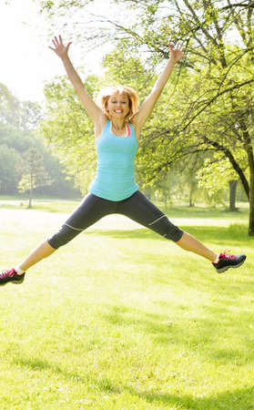 Happy female fitness instructor jumping exercising outside at green park photo