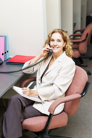 cubby: Businesswoman on phone taking notes in office workstation