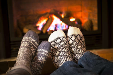 warm house: Feet in wool socks warming by cozy fire Stock Photo