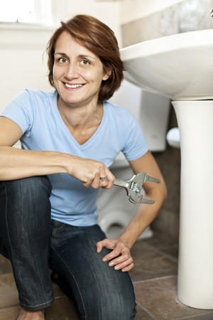Confident woman repairing sink in bathroom at home Stock Photo - 20785472