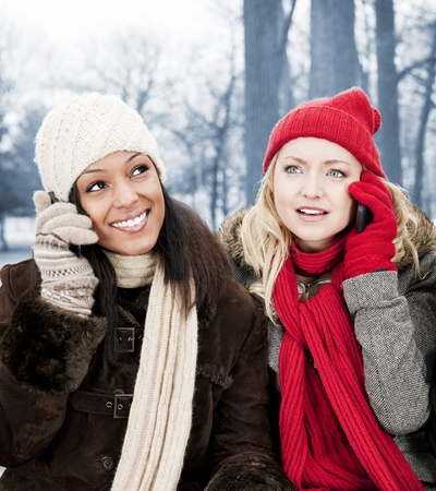 Portrait of two young female friends on the phone outdoors in winter Stock Photo - 20785481