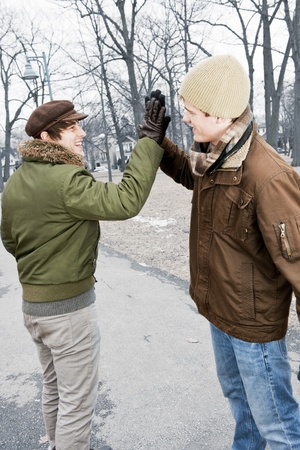 Two young men meeting in winter park giving high five photo