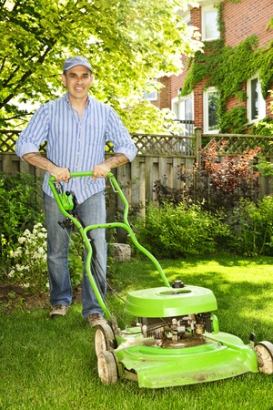 maintaining: Man with lawn mower in landscaped backyard Stock Photo