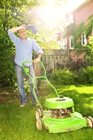 Man taking a break while mowing lawn on hot summer day Stock Photo