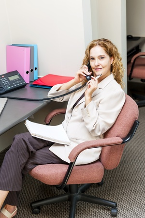 cubby: Thoughtful business woman on phone taking notes in office workstation