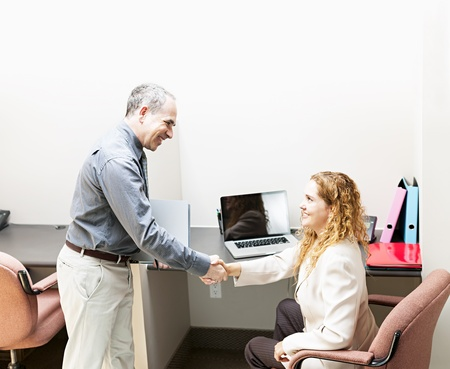 cubby: Man and woman meeting in office shaking hands Stock Photo
