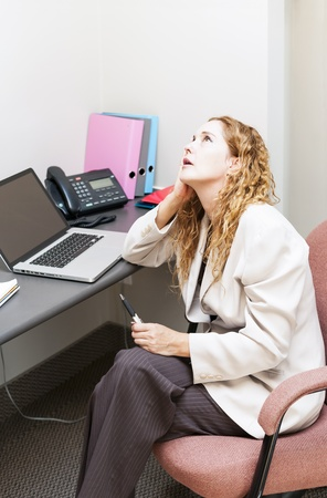 cubby: Businesswoman worried in office workstation looking up