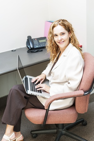 Confident businesswoman sitting at workstation in office with computer photo