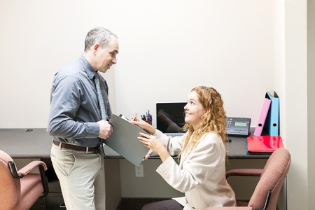 Man and woman meeting to discuss paperwork in office photo