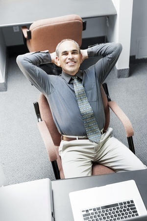 cubby: Businessman with laptop computer sitting at office workstation Stock Photo