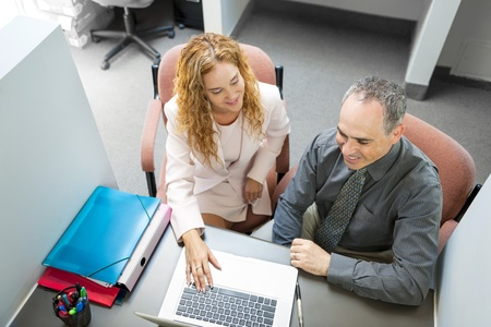office cubicle: Man and woman sitting at desk with computer in office