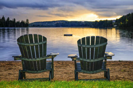 adirondack chair: Two wooden chairs on beach of relaxing lake at sunset. Algonquin provincial park, Canada.