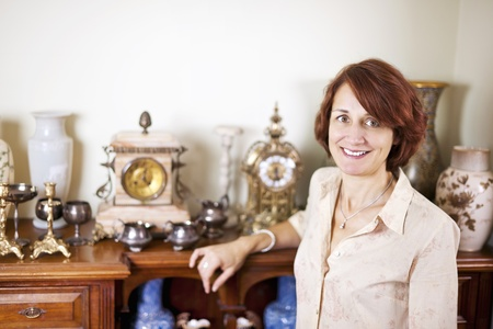 furniture store: Happy proud woman standing next to her collection of antiques