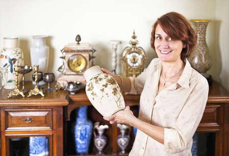 reloj antiguo: Mujer orgullosa que sostiene jarr�n de su colecci�n de antig�edades Foto de archivo